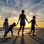 Familie bei Sonnenuntergang am Strand