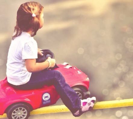 Mädchen fährt auf einem Rutschauto